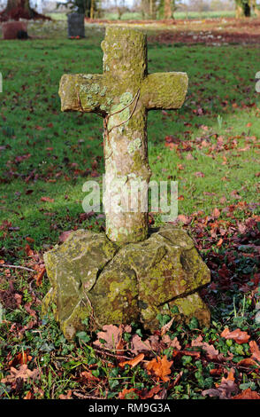 A grave marker cross in an English country churchyard at Shelton, Norfolk, England, United Kingdom, Europe. - Stock Image