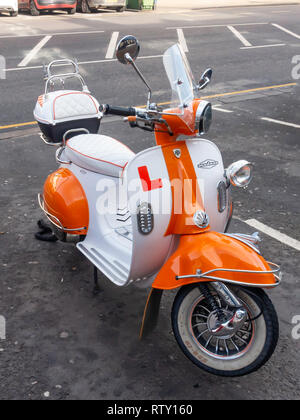 A smart well equipped White and Orange Vespa Modena motor scooter at Redcar North Yorkshire - Stock Image