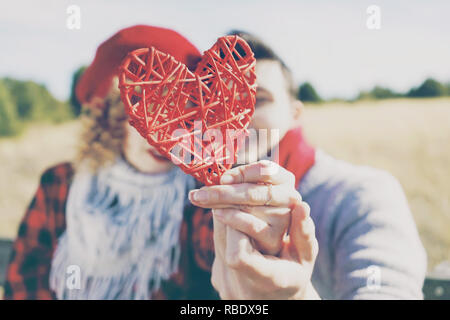 Lovely close-up of a beautiful red heart held by a romantic young couple in love in a nice bokeh as background outdoor. It reminds love or health care - Stock Image