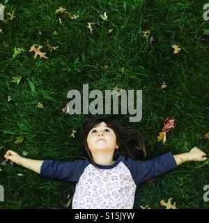 Young girl laying in the grass - Stock Image