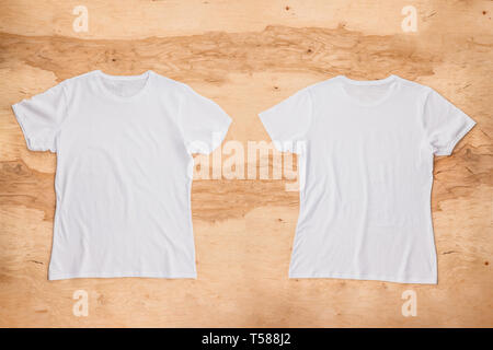 Front and back of white empty T-shirt on wooden background. Horizontal view. - Stock Image