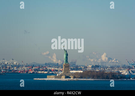 Statue of Liberty seen across New York Harbor on a sunny winters day. - Stock Image