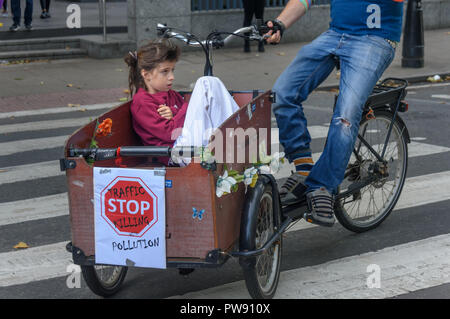 London, UK. 13th October 2018. A child  sits in a box on a bicycle and waits for the start of the funeral procession of cyclists behind a horse-drawn hearse to highlight the failure of governments from all the major parties to take comprehensive action on safer cycling. Stop Killing Cyclists call for £3 billion a year to be invested in a national protected cycling network and for urgent action to reduce the toxic air pollution from diesel and petrol vehicles which kills tens of thousands of people every year, and disables hundreds of thousands. The several hundred protesters staged a ten-minut - Stock Image