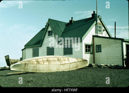 Eskimo Umiak in front of house; Point Barrow, Alaska.  Boat made of wood and skins, for transportation of goods, - Stock Image