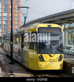 A yellow metrolink tram pulled up at a platform before departing to Manchester Piccadilly. - Stock Image