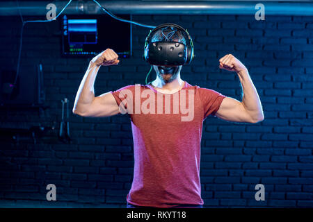 Portrait of a strong man playing with virtual reality headset in the dark room of the playing club - Stock Image
