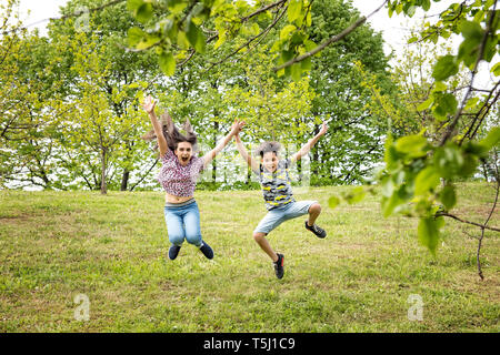 Cute energetic young brother and sister leaping together in a wooded park in spring celebrating the warmer weather - Stock Image