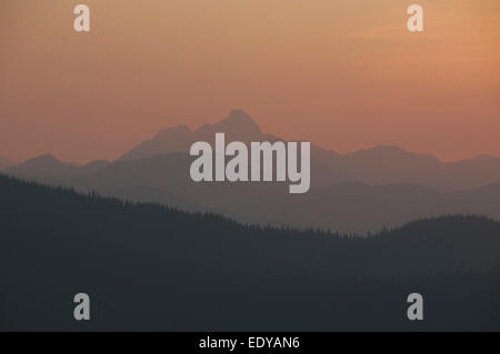 Dusk in the mountains with silhouetted mountains set in a clear but smoky, hazy sky - Stock Image