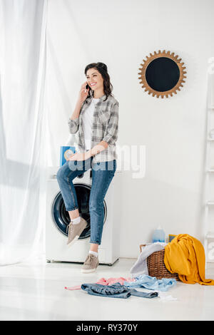 woman in grey shirt and jeans sitting on washer and talking on smartphone in laundry room - Stock Image