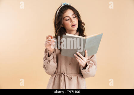 Image of beautiful young pretty woman posing isolated over beige background wall holding book reading. - Stock Image