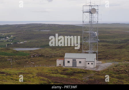 A view of a radio/television mast station in a wild landscape in northwest Scotland overlooking crofts - Stock Image