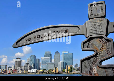 Arm of cast iron signpost funded by The Royal Bank of Scotland to mark Millennium with Thames & skyline of Canary Wharf in London Docklands England UK - Stock Image