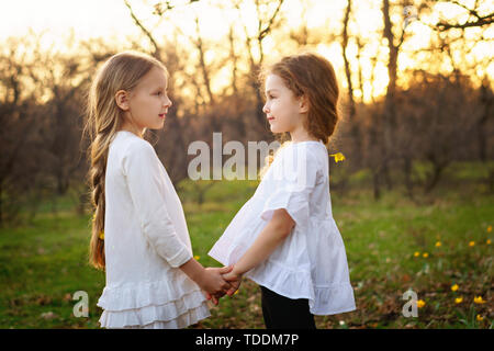 Cute little girls in white clothes looking at each other's eyes. Portrait of sisters in spring meadow. Friendship and trust concept - Stock Image