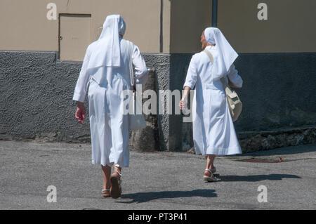 Two Catholic nuns walking through Domodossola, Piedmont, Italy - Stock Image