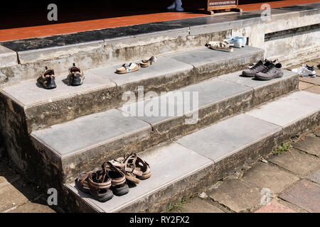 Visitors shoes left on steps outside a temple in Thien Mu Pagoda complex. Hue, Thừa Thien–Hue Province, Vietnam, Asia - Stock Image