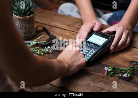 Cropped image of customer paying with credit card in flower shop - Stock Image