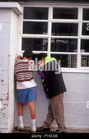 primary school boys playing hide and seek - Stock Image