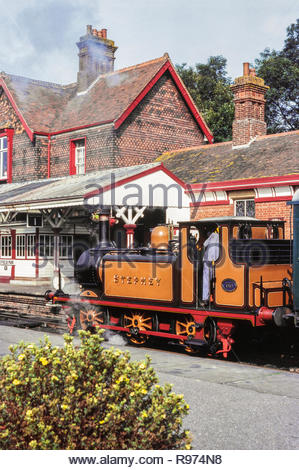 """A Stroudley Terrier 0-6-0T, No 55 """"Stepney"""" steam locomotive, in Stroudley Golden Ochre livery, heads a steam train at  Sheffield Park Station on the Bluebell Railway heritage railway Sussex England, UK in the 1980s – 1983 - Stock Image"""