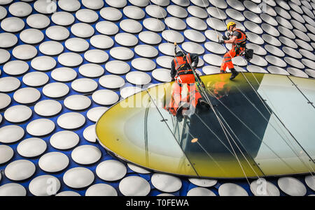 The Bull Ring, Birmingham, UK, 19th Mar 2019. A group of rope access contractors works at lofty heights on the famous facade of the Selfridges building in Birmingham's Bull Ring Shopping Centre. The work is part of a planned ongoing project. The Selfridges Building is covered in 15,000 spun aluminium discs on a blue background. Credit: Imageplotter/Alamy Live News - Stock Image