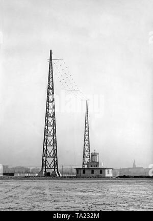Radio masts at the Tempelhof Airfield. The antenna wires are marked with flags for better visibility for the pilots. - Stock Image
