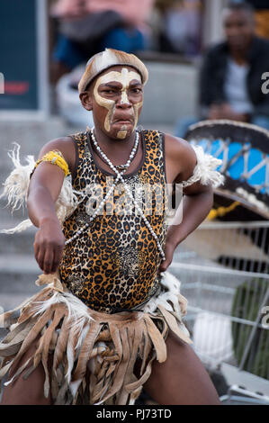 Man in tribal African clothes entertaining tourists on the streets of Cape Town, South Africa - Stock Image