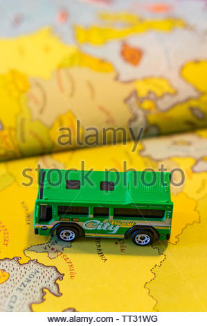Mattel Matchbox green toy city bus standing on a page with European map of a open atlas book on circa June 2019 in Poznan, Poland. - Stock Image