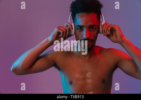 Portrait of shirtless african american man poising with headphones and looking at camera isolated over violet background - Stock Image
