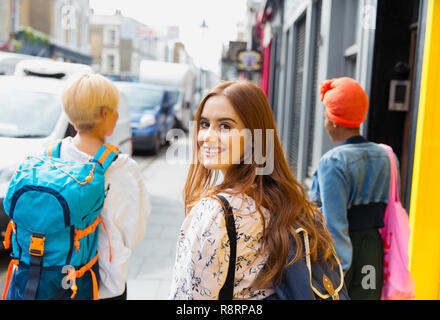 Portrait smiling, confident young woman with backpack on urban sidewalk - Stock Image