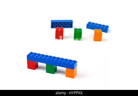 Steps to construct a bridge or viaduct model of Lego pieces. Blue bridge deck resting on three coloured piers. - Stock Image
