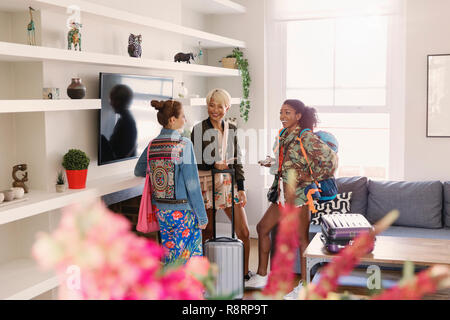 Young women friends with suitcases in house rental - Stock Image