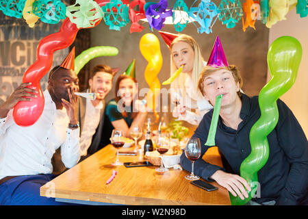Friends celebrate a party with colorful decoration in carnival or birthday - Stock Image
