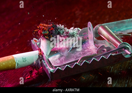 Mousetrap cutting a burning cigarette. - Stock Image