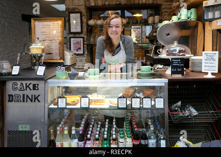 A smiling young woman worker serving food and drink in the contemporary Old Printing Office cafe restaurant in Llandovery Wales UK  KATHY DEWITT - Stock Image