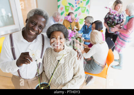 Portrait happy active senior couple enjoying flower arranging class - Stock Image