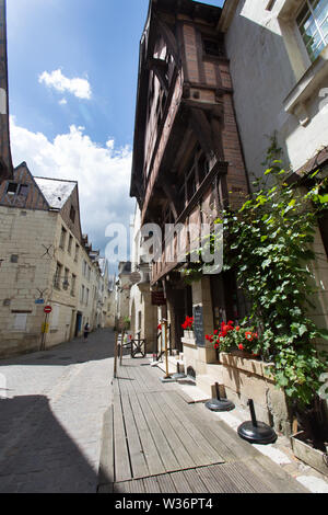 Chinon, France. Picturesque street view of Chinon's Rue Voltaire with a historic timber framed building in the foreground. The building is now being u - Stock Image