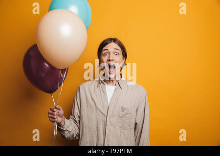 Cheerful teenage boy standing isolated over yellow background, holding bunch of air balloons - Stock Image