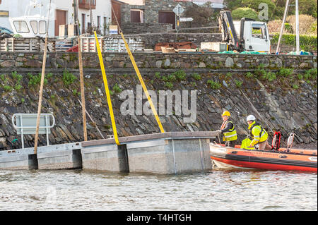 Schull, West Cork, Ireland. 16th Apr, 2019. West Cork Civil Engineering were given the task of refloating the €600,000 Schull pontoon, ready for the season.  Workers are seen lifting a piece of the pontoon into the water, ready to be floated into position. Credit: Andy Gibson/Alamy Live News. - Stock Image