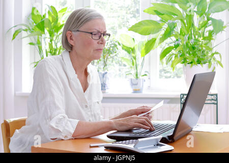 Annoyed senior woman at home with a calculator and lots of receipts in front of her laptop making her annual tax - Stock Image