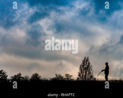 A man stood with a shotgun on a day's shooting in the evening light silhouetted against a stormy winter sky - Stock Image