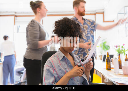 Creative female designer cutting photograph in office - Stock Image