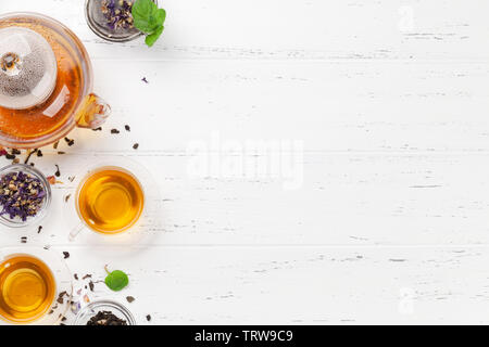 Different herbal and fruit dry teas, teapot and cups on wooden table. Top view flat lay with copy space - Stock Image