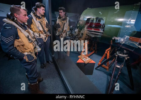 London, UK. 14th March, 2019. Re-enactors study a cut out of the bouncing bomb and recording equipment - Immersive Histories: Dambusters Virtual Reality Experience. An opportunity to step back in time to the early hours of 17 May 1943 and on board Avro Lancaster G-George to join the Dambusters on their legendary mission. Using the latest virtual reality and haptic technology, in conjunction with a physical 1:1 recreation of the interior of the iconic Avro Lancaster bomber, visitors will experience key events from the Dambusters Raid. Credit: Guy Bell/Alamy Live News - Stock Image