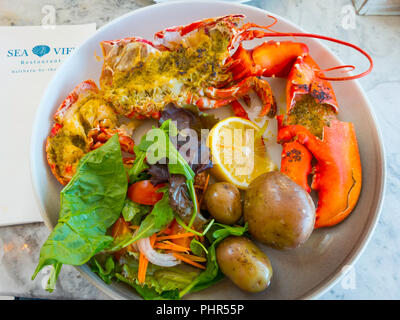 Half a Lobster served with fresh salad, new potatoes, garlic butter and a slice of lemon lunchtime meal at the Seaview Café Saltburn North Yorkshire - Stock Image