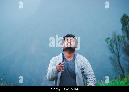Male completed his trekking and throwing his hat in the air and feeling refreshed - Stock Image