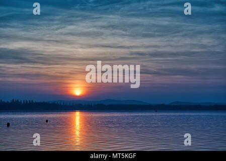 great sunset over the lake of Varese in autumn season with amazing cloudy sky - Stock Image