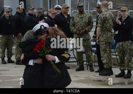 GROTON, Conn. (Mar. 15, 2019) Chief Electronics Technician Submarine Communications Eric Whitaker greets his two daughters, with the traditional first hug during a homecoming celebration for the Los Angeles-class, fast-attack submarine USS Providence  (SSN 719) at Naval Submarine Base New London in Groton, Conn. Providence is returning from the European Command Area of Responsibility where they executed the Chief of Naval Operations' Maritime Strategy in supporting national security interests and Maritime Security Operations. - Stock Image
