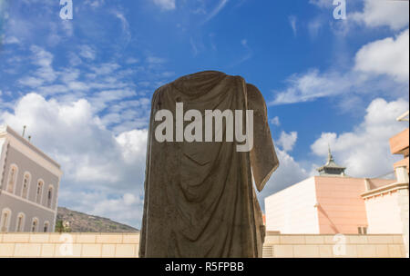 Cartagena, Spain - September 14th, 2018: Roman sculpture in front of the window of Museum of the Roman Theater of Cartagena,  Murcia, Spain - Stock Image