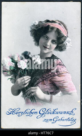 A greeting postcard printed in Germany, shows a beautiful woman with a bouquet of flowers. The inscription in German: - Stock Image