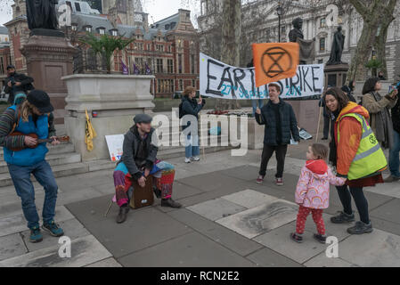 London, UK. 15th January 2019. Earth Strike UK campaigners in Parliament Square began the first of 4 international actions leading to a global General Strike on 27th September 2019, leaving work & school, boycotting non-necessary consumption and protesting in our streets to demand urgent change to halt global mass extinction, the destruction of our world by catastrophic climate change caused by greenhouse gases, mainly from using carbon fuels, coal, oil and gas. Credit: Peter Marshall/Alamy Live News - Stock Image