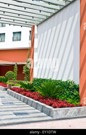 A colorful garden in the fgrounds of a modern building - Stock Image
